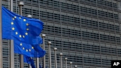 FILE - European Union flags set of half staff outside the European Commission headquarters in Brussels, Belgium.