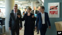German Interior Minister Thomas de Maiziere; Eva- Maria Kirschsieper, Facebook head of public policy; and Martin Ott, Facebook managing director central Europe, from left, walk during a visit at the Facebook office in Berlin, Germany, Aug. 29, 2016.