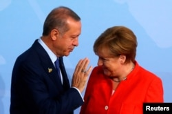 FILE - Turkish President Recep Tayyip Erdogan talks to German Chancellor Angela Merkel as he arrives for the G-20 leaders summit in Hamburg, Germany, July 7, 2017.