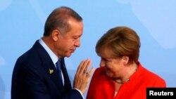 Le président turc Recep Tayyip Erdogan parle à la chancelière Angela Merkel à Hamburg, Allemagne, le 7 juillet 2017.