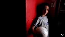 Candelaria Cabrera, 7, poses for a portrait holding a soccer ball in Chabas, Argentina, Sept. 8, 2018. She was 3 years old when her parents gave her her first ball. Her desire to play soccer has called attention to the obstacles women face in the sport in Argentina.