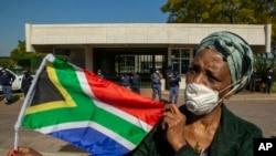 Seorang wanita memegang bendera nasional Afrika Selatan selama protes menentang rasisme di depan Kedutaan Besar AS di Pretoria, Afrika Selatan, Jumat, 5 Juni 2020. (Foto: AP)