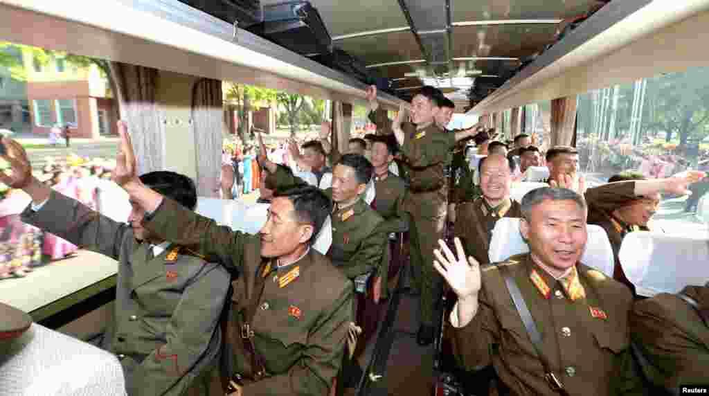 평양으로 초대받은 탄도미사일 '화성-12' 개발자들이 버스 안에서 손을 흔들고 있다.