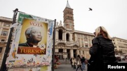 A woman looks at a poster supporting Cardinal Peter Turkson in front of the Papal Basilica of Saint Mary in Rome, March 1, 2013.