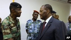 Ivory Coast's President Alassane Ouattara (R) shakes hands with General Philippe Mangou, chief of staff of former pro-Laurent Gbagbo Defense and Security Forces (FDS), at the Hotel du Golf in Abidjan, April 12, 2011