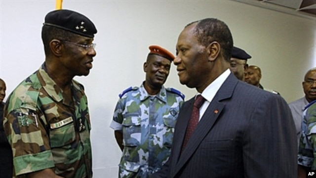 Ivory Coast's President Alassane Ouattara (R) shakes hands with General Philippe Mangou, chief of staff of former pro-Laurent Gbagbo Defense and Security Forces (FDS), at the Hotel du Golf in Abidjan, April 12, 2011 (file photo)
