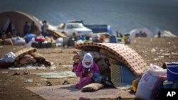 Seorang warga Suriah yang menyelamatkan diri dari pertempuran yang berkecamuk di desanya, beristirahat di sebuah wilayah penampungan Atma, dekat perbatasan Turki-Suriah (7/11). Pertempuran kembali pecah di dekat wilayah perbatasan Turki, Ceylenpinar menyebabkan semakin banyaknya pengungsi ke negara tetangga Suriah ini.