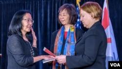 Sandy Sugawara is sworn in by VOA Director Amanda Bennett as VOA's new Deputy Director. Kelu Chao, Associate Director for Language Programming, holds the U.S. Constitution.