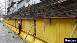 武漢被封的道路上一名戴口罩的工人試圖穿過障礙物。 (2020年3月9日)