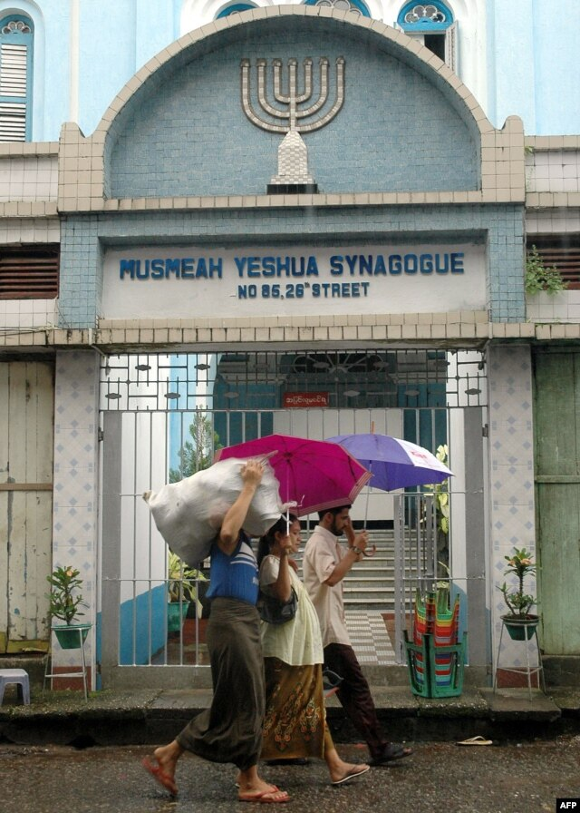 FILE - Residents walk past the Musmeah Yeshua Synagogue in downtown Rangoon, Oct. 2006.