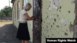 A school principal outside Ilovaisk's School Number 14. Due to the significant damage the school sustained during the conflict, it did not reopen for the 2015-2016 school year.