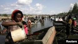 Penduduk desa berkumpul di sungai untuk mengolah lumpur yang mengandung emas, akibat bocornya pipa milik penambangan tembaga dan emas AS, Freeport McMoRan, di desa Kwanki Lama, provinsi Papua, 8 Oktober 2011. (Foto: dok).