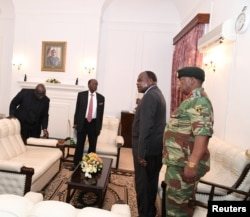 FILE - Mugabe meets with Father Fidelis Mukonori, Secretary to the Cabinet Dr Misheck Sibanda and Defense Forces Commander General Constantino Chiwenga at State House in Harare, Nov. 19, 2017.
