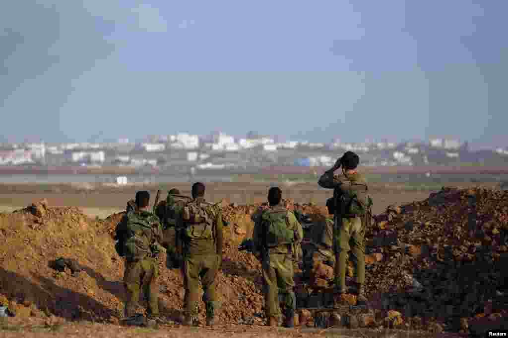 Israeli soldiers look towards Gaza from Israel.