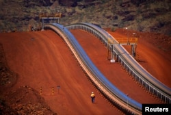 FILE - A worker walks near conveyer belts loaded with iron ore at the Fortescue Solomon iron ore mine located in the Valley of the Kings, around 400 km (248 miles) south of Port Hedland in the Pilbara region of Western Australia.