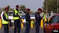 Polisi Bahrain melakukan pemeriksaan surat ijin pengendara mobil di ibukota Manama. Bahrain melakukan penumpasan protes anti pemerintah dengan keras.