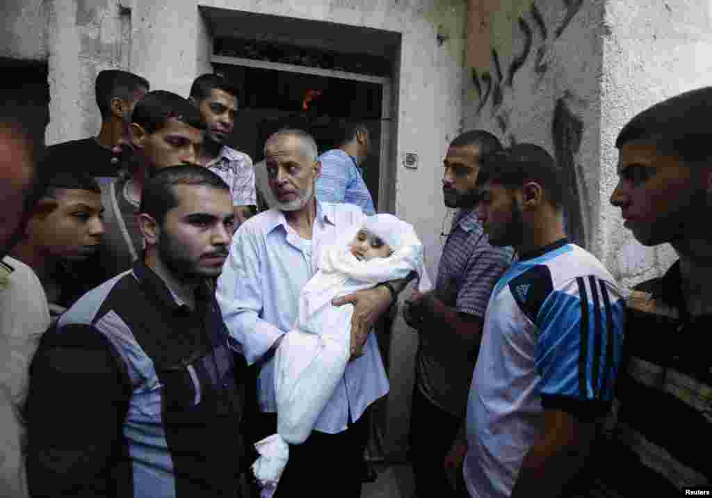 A relative of the wife of Hamas's military leader, Mohammed Deif, and his infant son Ali, whom medics said were killed in Israeli air strikes, carries Ali's body during the funeral, in the northern Gaza Strip, Aug. 20, 2014.