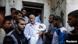 Hamas askeri liderinin hava saldırısında ölen küçük yaştaki oğlu Ali'nin naşı bir akrabası tarafından taşınırken