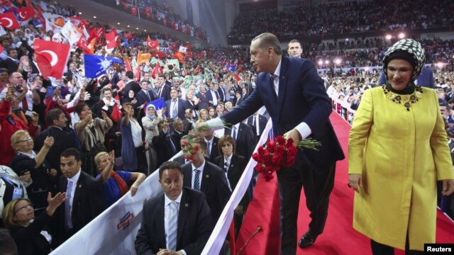 Turkey's PM and leader of ruling Justice and Development Party (AKP) Tayyip Erdogan, accompanied by his wife Emine Erdogan (R), throws carnations to supporters during his party congress in Ankara, September 30, 2012.