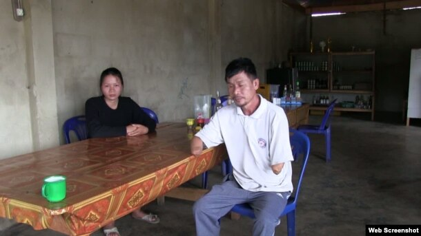Houng Phomma Chak sit at a table with his daughter. In 2004, he lost both of his lower arms and was blinded in one eye when a bomb exploded while he was out collecting the old casings to sell for scrap metal.