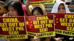FILE - Protesters picket the Chinese Consulate at the financial district of Makati city east of Manila, Philippines, March 3, 2014.