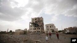 也门萨那居民站在一座被沙特领导的联军空袭炸毁的房屋前. (2015年7月6日)