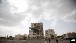 Warga berdiri di dekat sebuah gedung yang hancur akibat serangan udara pimpinan Saudi di Sana'a, Yaman (6/7).