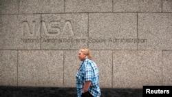 Seorang perempuan melewati kantor pusat NASA di luar kota Washington, DC.
