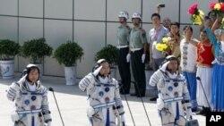 ນັກບິນອະວະກາດຈີນ ຈາກຊ້າຍຫາຂວາ Liu Yang, Jing Haipeng ແລະ Liu Wang ທຳການຄຳນັບ ກ່ອນຈະ ອອກເດີນທາງ ຂຶ້ນສູ່ວົງໂຄຈອນ ພ້ອມກັບຍານ Shenzhou 9 (16 ມິຖຸນາ 2012)