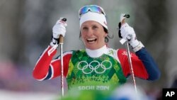 Norway's Marit Bjoergen celebrates winning the gold during the women's classical-style cross-country team sprint competitions at the 2014 Winter Olympics, Feb. 19, 2014, in Krasnaya Polyana, Russia.