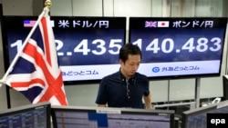 24일 일본 도쿄의 외환거래소에서 직원이 업무를 보고 있다. 그 뒤로 파운드 대비 엔화 환율을 나타낸 전광판이 걸려있다.