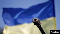 Moncong tank militer Ukraina di depan bendera negara itu terlihat di pos pemeriksaan di Mariupol, Ukraina. (Reuters/Marko Djurica)