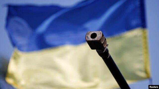 Дуло танка на фоне украинского флага
