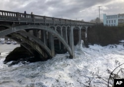 In this Jan. 11, 2020 photo heavy surf surrounds the legs of a bridge as an extreme high tide rolls into the harbor in Depoe Bay, Oregon, USA. (AP Photo/Gillian Flaccus)