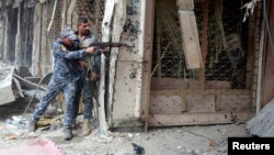 A member of the Iraqi Federal Police opens fire against Islamic State militants in the Old City of Mosul, Iraq July 7, 2017.