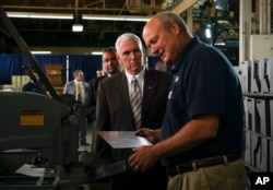 Vice President Mike Pence listens to a metal worker during a tour of an industrial facility in Ohio on June 28, 2017.
