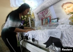 FILE - A woman pays her respects to slain transgender Jennifer Laude inside a funeral home in Olongapo city, north of Manila, Oct. 21, 2014.