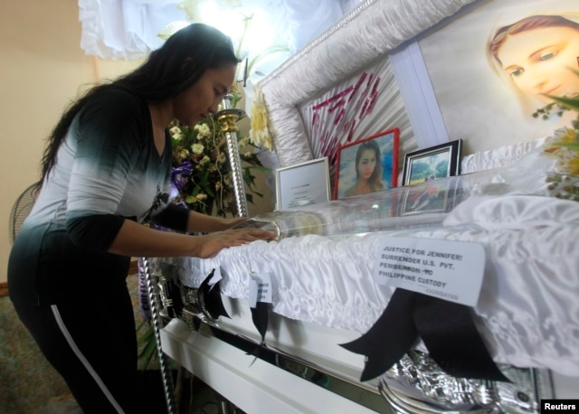 A woman pays her respects to slain transgender Jennifer Laude inside a funeral home in Olongapo city, north of Manila October 21, 2014. Philippine President Benigno Aquino rejected on Monday calls to tear up the Visiting Forces Agreement with the United S
