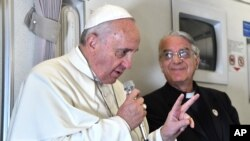 Paus Fransiskus berbicara dengan jurnalis dalam penerbangan dari Manila menuju Roma (19/1). (AP/Giuseppe Cacace)