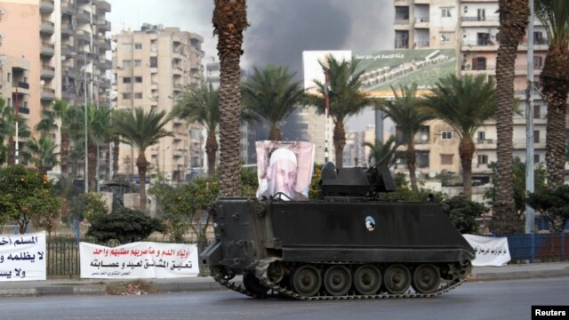 Smoke rises as a Lebanese Army armed vehicle drives through a street in Tripoli, northern Lebanon, Dec.1, 2013.