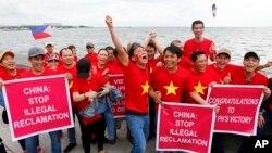 Kaum ekspatriat Vietnam bersorak sambil mengacungkan plakat selama terjadinya unjuk rasa di tepi jalur pejalan kaki sebelum pengadilan arbitrase internasional PBB yang berpusat di Den Hague mengumumkan keputusannya terkait dengan sengketa di Laut China Selatan, Selasa (12/7).
