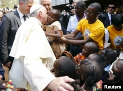 Pope Francis kisses a child as he visits the refugee camp of Saint Sauveur in the capital Bangui, Central African Republic, Nov. 29, 2015.