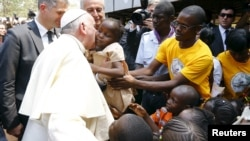 Papa Francis Francis kisses a child as he visits the refugee camp of Saint Sauveur in the capital Bangui, Central African Republic, Nov. 29, 2015.