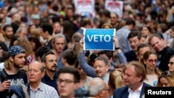 "A demonstrator holds up a banner saying ""Veto"" during a rally against a new law passed by Hungarian parliament that forces the Soros-founded Central European University out of Hungary, in Budapest, April 4, 2017"
