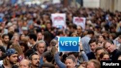 "Seorang pengunjuk rasa mengangkat poster yang berbunyi ""Veto"" selama rapat akbar, menentang undang-undang baru yang disetujui oleh parlemen Hungaria yang dapat memaksa Central European University yang didirikan oleh Soros keluar dari Hungraria, yang diselenggarakan di Budapest, tanggal 4 April 2017 (foto: REUTERS/Laszlo Balogh)"