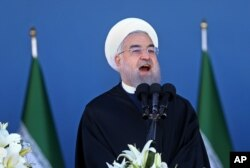 FILE - Iran's President Hassan Rouhani speaks at a military parade marking National Army Day in front of the mausoleum of the late revolutionary founder Ayatollah Khomeini, just outside Tehran, April 17, 2016.