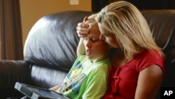 FILE - A mother is seen with her 11-year-old autistic son.