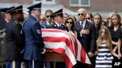FILE - Vice President Joe Biden, accompanied by his family, watches an honor guard carry a casket containing the remains of his son Beau Biden into a funeral service at St. Anthony of Padua Roman Catholic Church in Wilmington, Del., June 6, 2015.