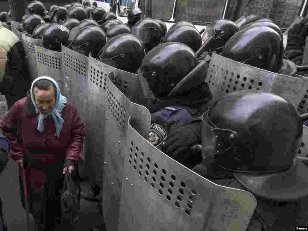 A woman passes by Interior Ministry personnel as they block pro-EU demonstrators near the Ukrainian Ministry of Internal Affairs in Kyiv, Ukraine, Dec. 20, 2013.