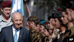 Israeli President Shimon Peres, second left, surveys the honor guard with Israeli Defense Forces Chief of Staff Benny Ganz, left, during Israel's 63rd Independence Day event at his residence, in Jerusalem, Tuesday, May 10, 2011.